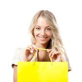 Blonde woman holding yellow shopping bag — Stock Photo