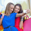 Two woman taking pictures of themselves - Stock Photo