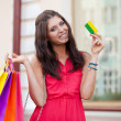 Woman holding credit card and bags — Stock Photo