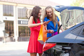 Two girls are piling the bags in the car — Stock Photo