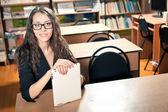 Kobieta siedzi za biurkiem w bibliotece — Zdjęcie stockowe