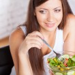 Beautiful brunette woman eating salad — Foto de Stock