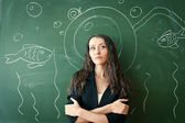 Girl over chalkboard with funny picture — Stock Photo
