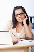 Businesswoman sitting behind the desk — Stock Photo