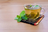 Green tea with mint on wooden table — Stock Photo
