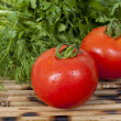 Two tomatoes and greens — Stock Photo