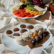 Assortment of fresh fruits and chocolate candies - Stock Photo