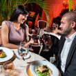 Beautiful couple with glasses of red wine at restaurant — Stock Photo