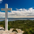 Stock Photo: White cross against blue sky and fluffy clouds