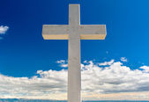 White cross against blue sky and fluffy clouds — Stock Photo
