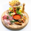 Abundance of raw food on a wooden board and basket of bread — Foto de Stock
