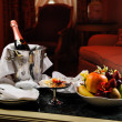 Romantic evening with bottle of champagne, sweets and fruits in — Stock Photo