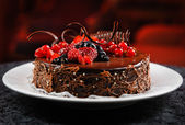 Delicioso pastel de chocolate con frutas frescas sobre una placa — Foto de Stock
