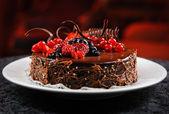 Lahodný čokoládový dort s čerstvým ovocem na talíři — Stock fotografie