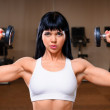 Beautiful young woman working out in fitness club — Stock Photo