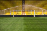 Empty stadium goal and sprinklers — Stock Photo