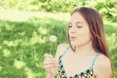 Woman blowing on dandelion — Stock Photo