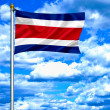 Costa Rica waving flag against blue sky — Stock Photo