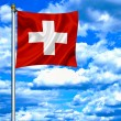 Swiss waving flag against blue sky — Stock Photo