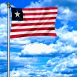 Liberia waving flag against blue sky — ストック写真