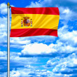 Spain waving flag against blue sky - Stok fotoğraf