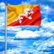 Bhutan waving flag against blue sky - Stok fotoğraf