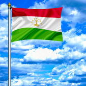 Tajiquistão acenando a bandeira contra o céu azul — Fotografia Stock