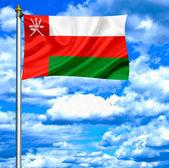 оман, размахивая флагом против голубого неба — Стоковое фото
