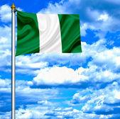 Nigeria waving flag against blue sky — Stock Photo