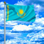 Kazakhstan waving flag against blue sky — Stock Photo