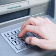 Hand entering PIN numbers on ATM bank machine — Stock Photo