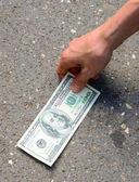 Hand picking money from street floor - Finding money on street c — Stock Photo