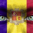 Human face painted with flag of Andorra — Stock Photo