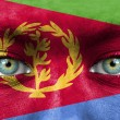 Human face painted with flag of Eritrea - Stock Photo