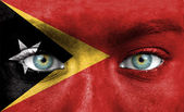 Human face painted with flag of East Timor — Stock Photo