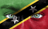 Human face painted with flag of Saint Kitts and Nevis — Stock Photo