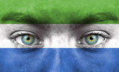 Human face painted with flag of Sierra Leone — Stock Photo
