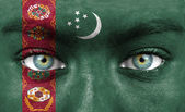 Human face painted with flag of Turkmenistan — Stock Photo