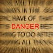 Blured text on vintage paper with focus on DANGER — Lizenzfreies Foto