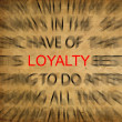 Blured text on vintage paper with focus on LOYALTY - Stock Photo
