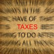 Blured text on vintage paper with focus on TAXES — Foto Stock #11488614