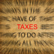 Blured text on vintage paper with focus on TAXES - Stock Photo