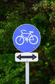 Bicycle sign in park with arrow in both directions — Stock Photo