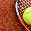 Tennis ball and racquet on clay macro shot - Stock Photo