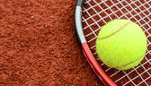 Tennis ball and racquet on clay macro shot — Stock Photo