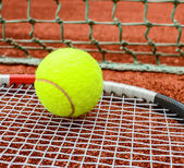 Tennis racket with ball on it clay on clay court — Stock Photo