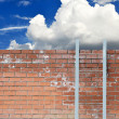 Ladder against a wall and blue sky with white clouds - Stock Photo