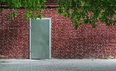 Gray old metal door texture with iron handle and brick wall arou — Stock Photo