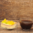 Close-up of glass cup of coffee and apricot cake on wooden table — Stock Photo