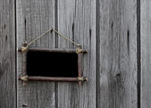 Wooden board hanging on the wall — Stockfoto